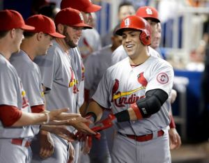 Carlos Beltran gets high fives after 1 of his 2 homers in the games, as the Cards beat the Marlins 13-7